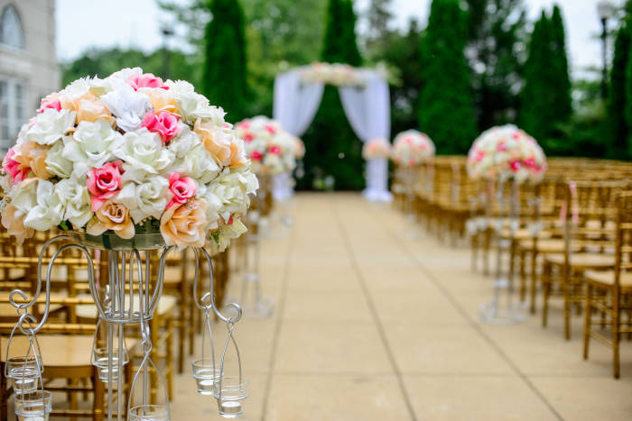 An outside ceremony setup, with floral arrangements along the aisle